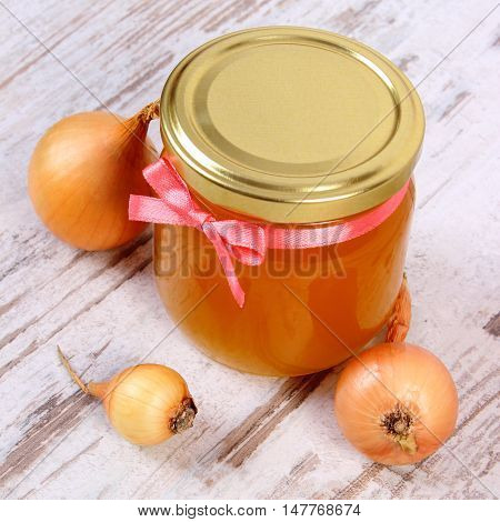 Fresh organic honey in glass jar and onions on old rustic wooden background healthy nutrition strengthening immunity and treatment of colds and flu