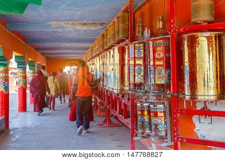 Buddhist nun walking touch a prayer wheels around the sanctuary at Larung gar (Buddhist Academy) in Sichuan China. This is the public place