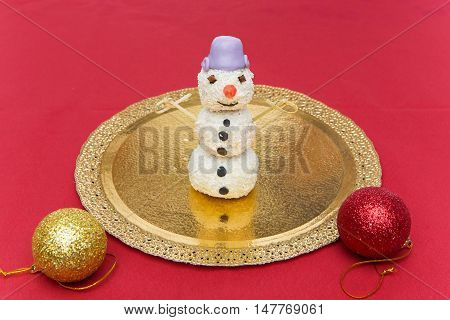 Christmas cake pop dessert in shape of snowman standing on golden folio plate. Copy space.