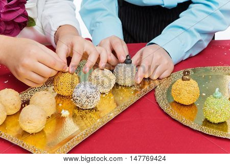 Children making new year cake pop dessert in shape of christmas tree balls