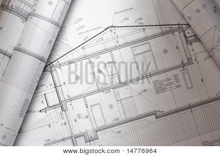 House plan blueprints roled up over table
