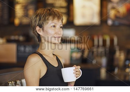 young Chinese woman enjoying coffee in coffee shop