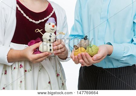 Children holding christmas cake pop dessert in shape of new year tree balls. Closeup.