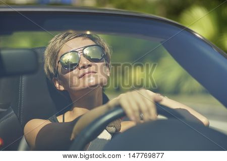 young asian woman driving a convertible car
