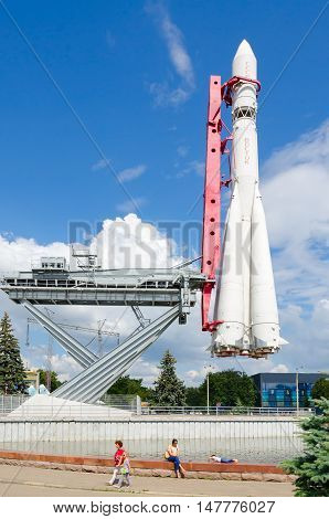 MOSCOW RUSSIA - JULY 23 2016: Unidentified people visit Exhibition of Economic Achievements in Moscow. Model of carrier rocket Vostok on Industry square of Exhibition of Achievements of National Economy