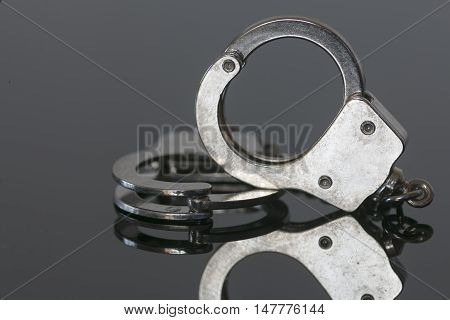 shiny handcuffs on black background with reflection