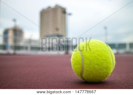 Tennis ball on tennis court on roof of a building