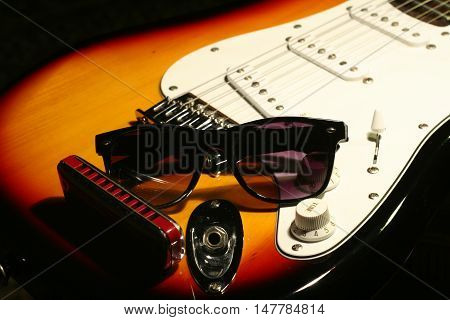 Vintage Electric Guitar, Harmonica, Sunglasses On Black Background