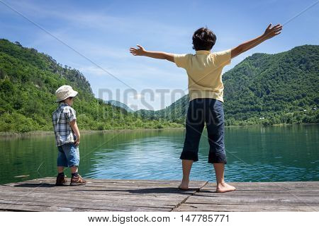 Happy kids on summer vacation having fun and happy time next to the mountain lake