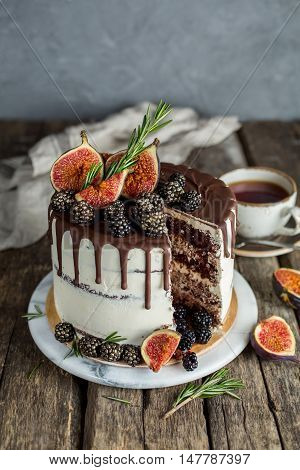 Chocolate cake with a cut piece. Delicious chocolate cake with figs and blackberries