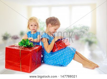 Two charming little girls , sisters, in identical blue dresses with polka dots. Girl looking at gifts Packed in beautiful red paper tied with a bow.On the background of the school hall with large Windows.