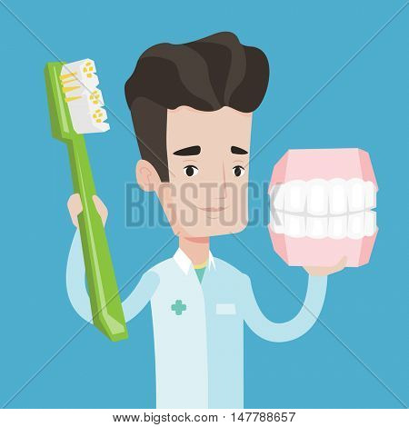 Young friendly dentist holding dental jaw model and a toothbrush in hands. Male dentist showing dental jaw model and toothbrush. Vector flat design illustration. Square layout.