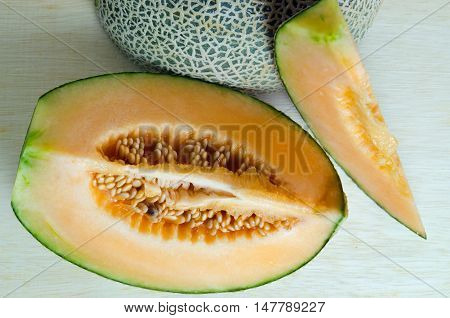 Cantaloupe Or Charentais Melon With Half And Seeds On Wooden Board Background