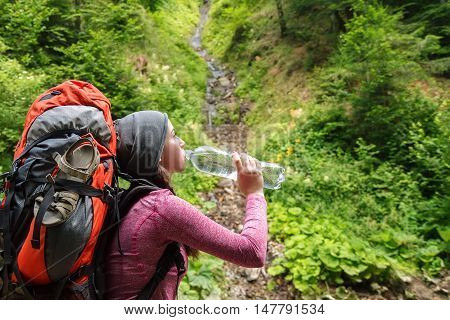Hiker girl drinking water. Woman tourist with backpack drinking water in nature. Young tourist woman drinking water outdoor forest and source of spring water on the background. Woman with bottle of water