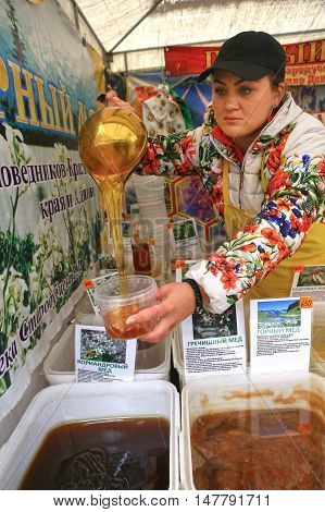 Moscow Russia - 19 2016: Unidentified woman sell honey on annual autumn famouse biggest honey fair in Moscow September 19 2016