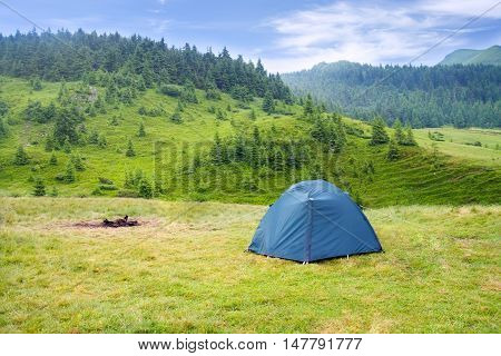 View of tent on meadow in mountains. Camping background. Camping and tent. Tourist tent on meadow green pine forest mountains and sky on the background. Adventure travel active lifestyle freedom outdoors.