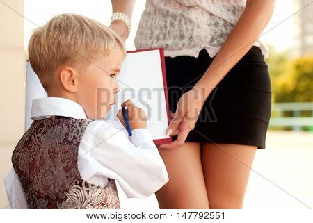 Baby blond businessman examines blueprints on the tablet using his mother. Education and business
