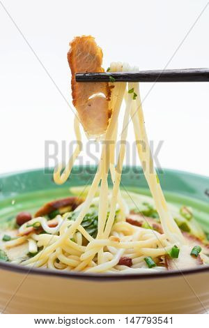 picking up piece of bbq prok with chopsticks from bowl of guilin rice noodles on white