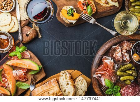 Italian antipasti wine snacks set. Brushettas, cheese variety, Mediterranean olives, pickles, Prosciutto di Parma with melon, salami and wine in glasses over black grunge background, top view, copy space