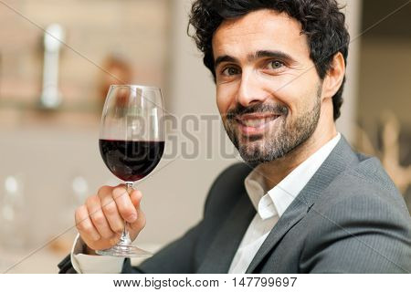 Handsome man tasting a glass of red wine