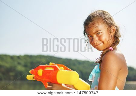 Girl playing with a squirt gun on the summer holidays