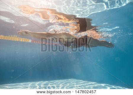 Stylish girl swims in crawl style underwater in the swim pool outdoors. She wears black-gray swimsuit, white swim cap and swim glasses. Sunlight falls from above. Her body reflected in water surface.