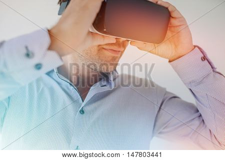 Closeup shot of businessman wearing virtual reality goggles against grey background. Young man using VR glasses with sun flare effect.