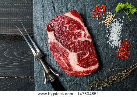 Raw fresh meat ribeye steak, chili pepper, salt and thyme on slate with meat fork on dark wooden background, top view