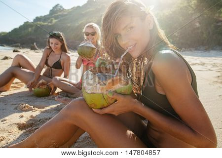 Portrait of beautiful young woman drinking fresh coconut water with her friends sitting in background on the beach. Group of young people enjoying summer vacation on beach.