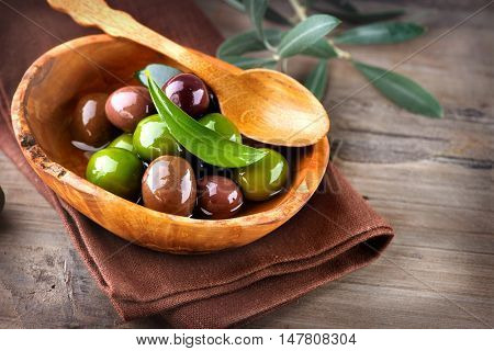 Olives and Olive Oil on wooden rustic table. Healthy green and black olives closeup