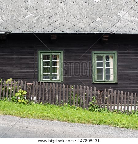 Authentic rustic nd brown mountain cottage front with windows and stones in Orlicke Mountains, Czech republic, Europe