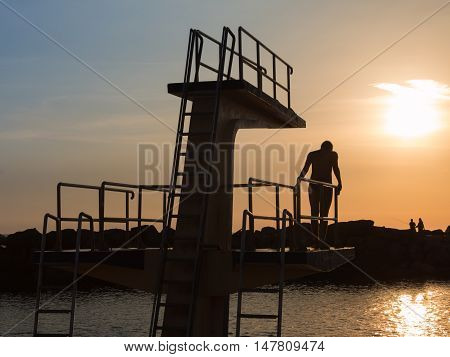 Man in Silhouette Hesitating in Jumping from High Board into Water