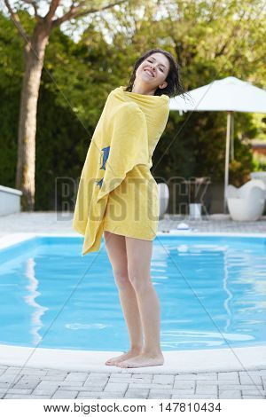 eautiful sexy woman wiping legs with towel after swimming pool