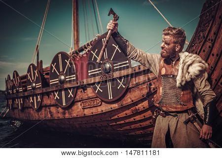 Viking warrior with axes standing near Drakkar on the seashore.