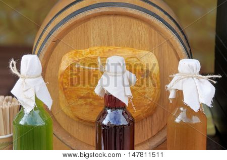 Bottles of homemade liqueurs on the background of wooden barrels