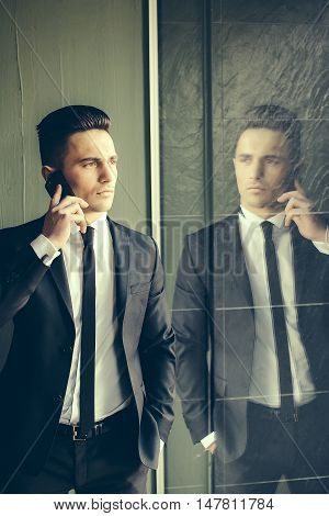 Man young handsome sensual elegant model in suit with skinny necktie open coat talks on mobile phone looks away hand in pocket reflects in mirror on grey background