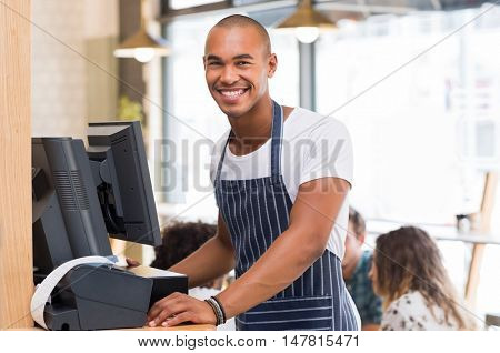 Portrait of cheerful young waiter looking at camera while printing bill. Happy smiling waiter waiting for bill to print. African waiter working at cafeteria and printing the receipt.