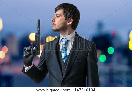 Hitman Or Assassin Holds Pistol With Silencer In Hand At Dusk.