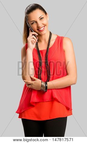 Beautiful woman making a phone cal l and smiling, isolated over gray background