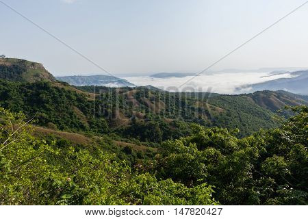 Clouds mist moves through rural valley hills covering scenic landscape.