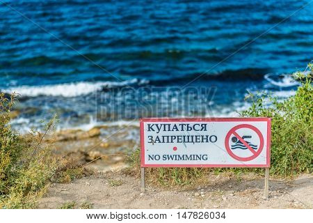 Red no swimming sign posted on the beach