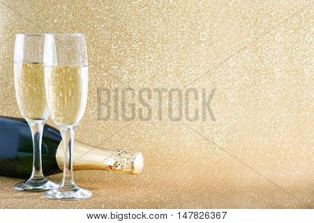 Champagne bottle with glass cups on brilliant golden background
