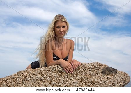 A beautiful blonde haired woman lying on a rock at the beach in her one piece looking at the camera seductively