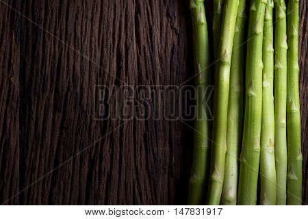 Bunches of asparagus on a wood background.