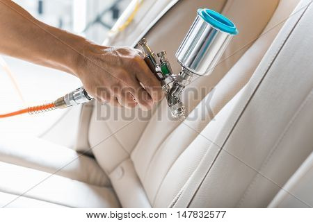 Car detailing series : Closeup of hand coating beige luxury car seat