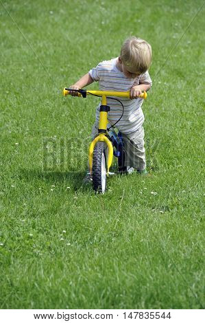 Child boy riding on his first bike. Bike without pedals. Child learning to ride and balance on his two wheeler bike with no pedals.
