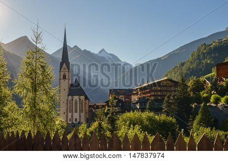 St Vincent church against Grossglockner mountain and Hohe Tauern range sunlit by evening sun. Heiligenblut Carinthia Austria