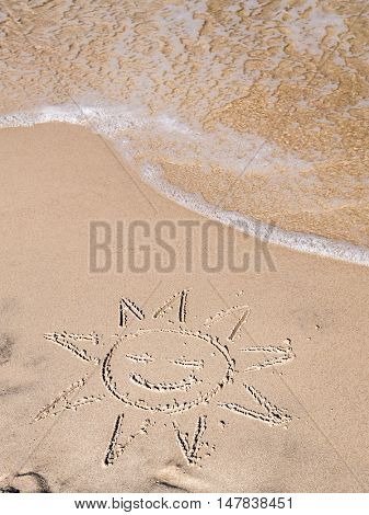 Finger drawn sun on sandy beach