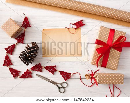 Creative diy hobby. Handmade tools for making christmas present, box in craft gift paper with red ribbon. Top view of white wooden table with copy space on sheet of paper, decoration of gift.