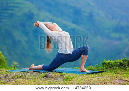 Yoga outdoors - sporty fit woman practices Hatha yoga asana Anjaneyasana - low crescent lunge pose posture outdoors in Himalayas mountains